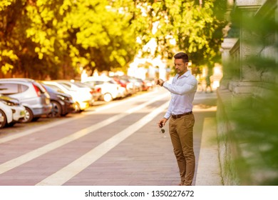 A handsome young businessman standing on the streets and checking the time on his wristwatch.