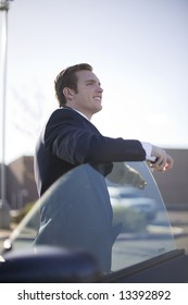 handsome young businessman standing outside of car with door open