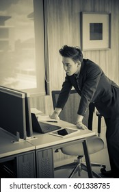 Handsome young businessman is stressful to work, check the work from a laptop,sepia tone,black and white,dark tone