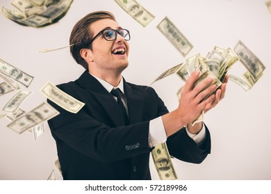 Handsome young businessman in suit and glasses is catching cash and smiling, on gray background