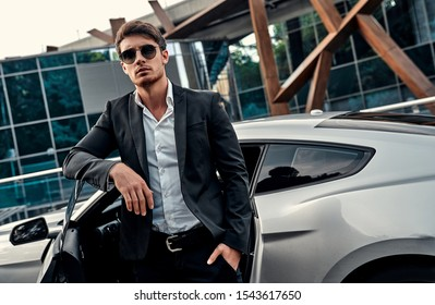 Handsome young businessman in suit is standing near his sport car in front of modern business center