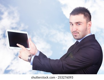 Handsome and young businessman with a tablet computer. Lens flare
