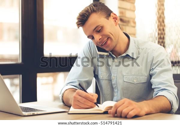 Un buen joven hombre de negocios está hablando por teléfono móvil, haciendo notas y sonriendo mientras trabaja en la oficina