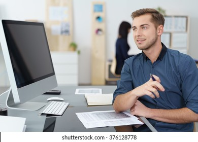 Handsome young businessman with a thoughtful expression sitting at his desk looking across at his blank computer monitor visible to the camera