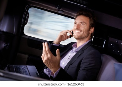 Handsome young businessman traveling in limousine, working on laptop computer, talking on mobile phone, smiling.