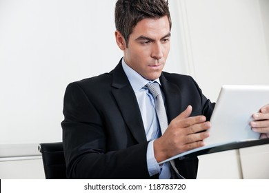 Handsome young businessman using digital tablet in office
