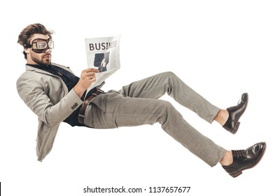 handsome young businessman in vintage aviation goggles reading newspaper while falling isolated on white