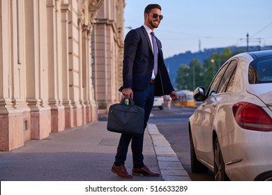 A handsome young businessman walking to his car