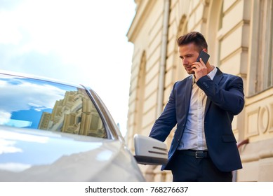 A handsome young businessman walking to his car on the street while talking on his phone