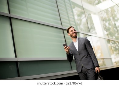 Handsome young businessman walking with mobile phone in front of office building