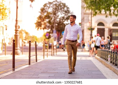 A handsome young businessman walking on the streets and covering his face on a sunny day.