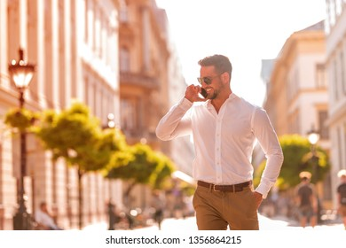 A handsome young businessman walking on the streets and talking on his phone on a sunny day.