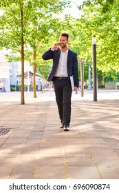 A handsome young businessman walking on the sunny street surrounded by trees while holding his laptop and talking on a phone
