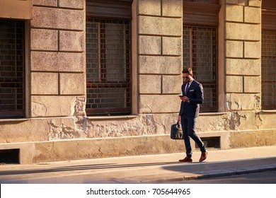 A handsome young businessman walking on the street in the sunset