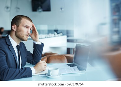Handsome young businessman wearing formal attire working during coffee break in modern restaurant hall:  looking up from documents with tired and thoughtful expression, rubbing his forehead