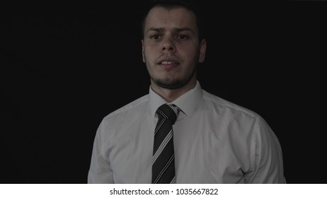 Handsome young businessman in white shirt, black background.