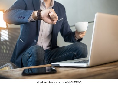 Handsome young businessman working at laptop with cup of coffee in restaurant. And looking at watch