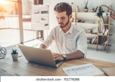 Handsome young businessman is working with laptop in modern light office. Successful confident man during work.