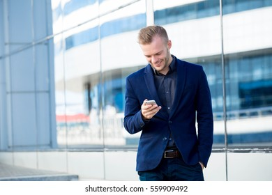 Handsome young businessman writes in the phone on the background of a glass building