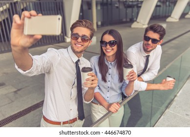 Handsome young businessmen and lady in sun glasses are holding coffee, making selfie using smart phone and smiling, standing on balcony of the office building