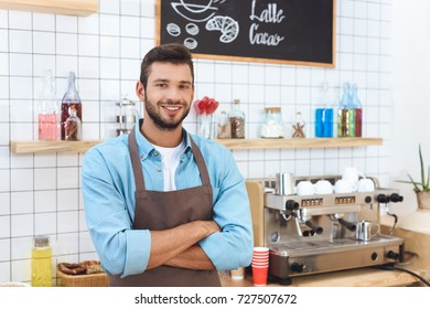 handsome young cafe owner in apron standing with crossed arms and smiling at camera
