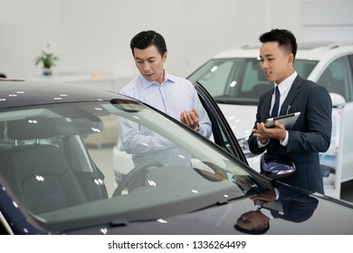 Handsome young car dealership worker showing car to middle-aged customer