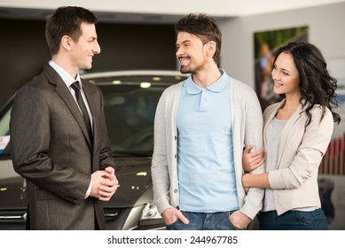 Handsome young car salesman is standing at the dealership telling about the features of the car to the customers.