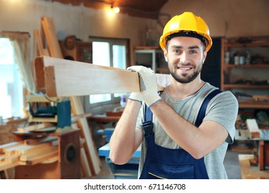 Handsome young carpenter with boards in workshop