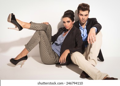 Handsome young casual man sitting on the floor while his girlfriend is leaning on him.
