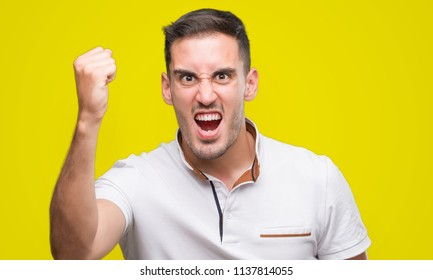 Handsome young casual man wearing white t-shirt annoyed and frustrated shouting with anger, crazy and yelling with raised hand, anger concept