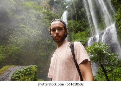 77a0e1d5224 Handsome young Caucasian male backpacker wearing t-shirt and baseball cap  backwards looking down at