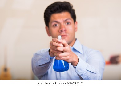 Handsome young caucasian male pointing cleaning spray bottle in front of him
