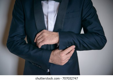Handsome, young Caucasian male wearing classy dark suit and fixing elegantly the suit sleeve. Horizontal detailed shot of man's hand gesture in adjusting the cufflinks or buttons of his sleeve.