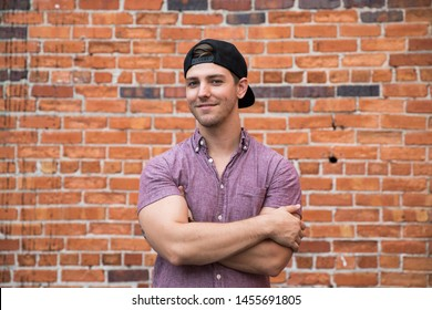 Handsome Young Caucasian Man with Backwards Hat Smiling for Portraits in Front of Textured Brick Wall Outside