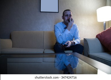 Handsome young caucasian man in a blue shirt and bow tie watching TV crying