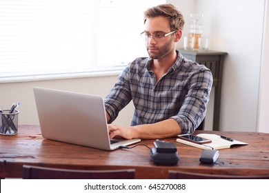 Handsome young caucasian man busy working from home, typing away on his notebook trying to write his latest novel and make it feel complete.