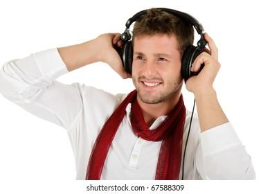Handsome young caucasian man listening music in headphones. Studio shot. White background.