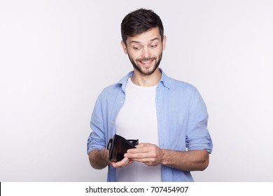 Handsome young  Caucasian man looking at his wallet with confident pleased face expression. Bearded hipster is happy to get his salary, going to invite his lady for a date. Business, money, emotions.