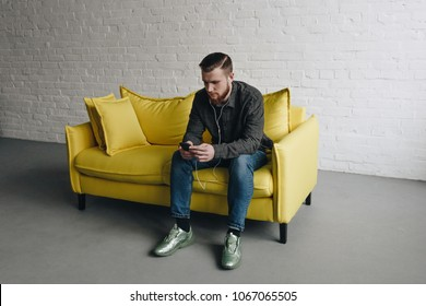 Handsome young caucasian man sitting on yellow couch