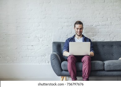 Handsome young Caucasian man sitting and typing on laptop.