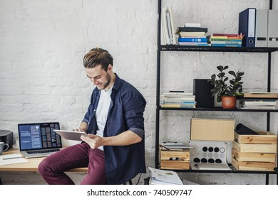 Handsome young Caucasian smiling businessman sitting at office and typing on tablet.