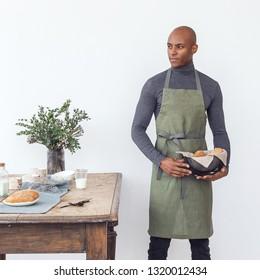 Handsome young chef wearing linen apron, preparing food. Brazilian model.