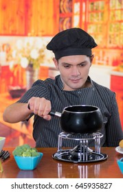 Handsome young cheff preparing a gourmet Swiss fondue dinner with assorted cheeses and a heated pot of cheese fondue and broccoli inside of a magenta bowls on wooden table in kitchen background
