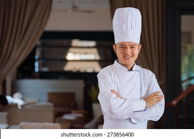 Handsome young cook in a restaurant smiling and looking at the camera