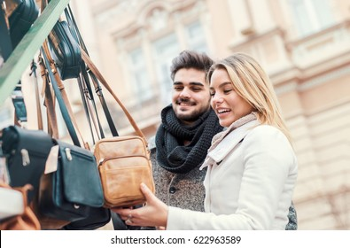 Handsome young couple walking through market and watching bags on the stall at street vendor. Dating, love, consumerism, shopping, lifestyle concept