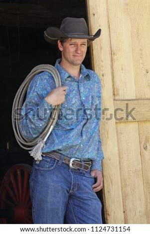43df02c4c2ebf Handsome young cowboy posed against barn door with lasso over shoulder