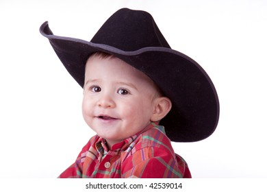 Handsome young cowboy toddler smiling while wearing a cowboy hat.