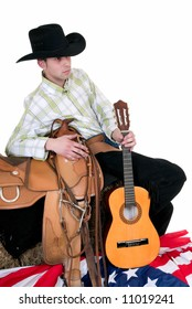 Handsome young cowboy with traditional outfit next to American flag, holding guitar.  Studio shot, white background.