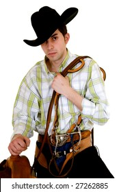 Handsome young cowboy with traditional outfit next to saddle holding rein.  Studio shot, white background.