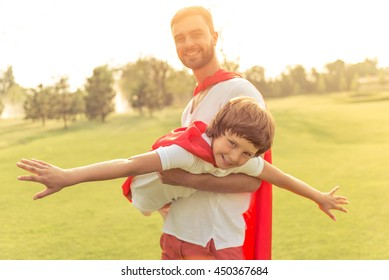 Handsome young dad and his cute little son dressed like superheroes are looking camera and smiling while playing in park. Father is holding his son in arms